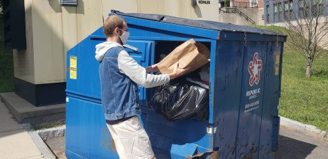 FSU student Peter Wade tries to fit his trash into a full dumpster