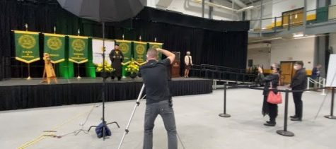 A 2021 graduate poses for a picture on the graduation stage, as his family proudly watches and cheers him on. Photo courtesy of Jordan Costa.